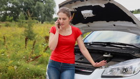 Ilsket anseende för ung kvinna på det brutna medlet och kalla bilreparationsservice stock video