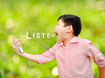 Ilsket asiatiskt barn som ropar på mobiltelefonen Arkivbild