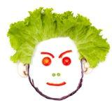 Ilsket mänskligt huvud som göras av grönsaker Arkivbild