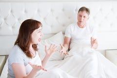 Ilsket ropa för Caucasian mellersta ålderfamiljpar i säng Konfliktförhållandebegrepp Make- och frudialog selektivt royaltyfri foto