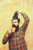 Ilsket skäggigt hår för maninnehavfrans och orange kopp arkivfoton