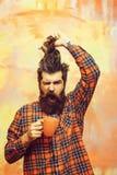 Ilsket skäggigt hår för maninnehavfrans och orange kopp arkivbilder