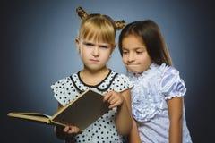 Ilskna eller stressade flickor med boken barn på grå bakgrund studiebegrepp arkivfoto