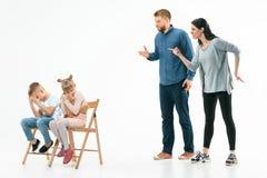 Ilskna föräldrar som hemma grälar på deras barn arkivfoto
