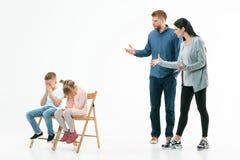 Ilskna föräldrar som hemma grälar på deras barn royaltyfria foton