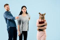 Ilskna föräldrar som hemma grälar på deras dotter arkivfoton