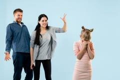 Ilskna föräldrar som hemma grälar på deras dotter royaltyfri foto