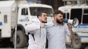 Ilskna fotbollsfan skriker på gatan i en megafon Caucasian folk på slag stock video