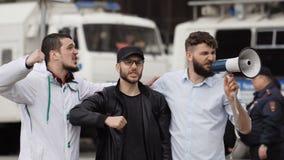 Ilskna fotbollsfan skriker på gatan i en megafon Caucasian folk på slag arkivfilmer