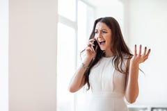 Ilskna härliga kvinnaskrin i mobiltelefon royaltyfri foto