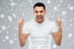Ilskna hållande nävar för ung man över snö arkivfoton