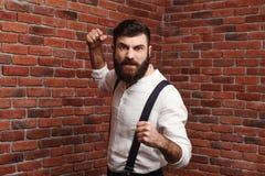 Ilskna nävar för visning för ung man för ursinne som poserar över tegelstenbakgrund royaltyfria foton
