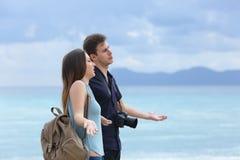 Ilskna par av turister som klagar om dåligt väder fotografering för bildbyråer