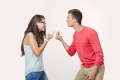 Ilskna par som argumenterar att skrika till varandra Studio som skjutas på vitbakgrund Disharmoni i förhållandet divergens royaltyfri foto