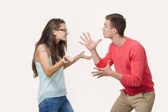 Ilskna par som argumenterar att skrika till varandra Studio som skjutas på vitbakgrund Disharmoni i förhållandet divergens royaltyfri fotografi