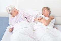 Ilskna par som ligger på säng royaltyfri fotografi