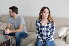 Ilskna par som separat sitter på soffan som ignorerar sig arkivfoto