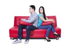 Ilskna par som tillbaka sitter för att dra tillbaka Royaltyfri Foto