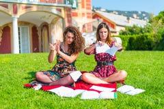 Ilskna studenter som upp river läroböcker royaltyfri foto