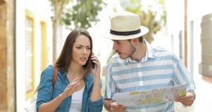 Ilskna turister som fordrar på telefonen i gatan