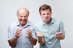 ilskna två män utropar med negativa sinnesrörelser ropar högt, över den vita studioväggen Den förargade sonen och fadern har fel arkivbilder