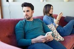 Ilskna unga par som ignorerar sig som anv?nder telefonen efter ett argument, medan sitta p? soffan hemma arkivfoton