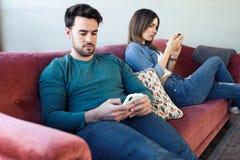 Ilskna unga par som ignorerar sig som anv?nder telefonen efter ett argument, medan sitta p? soffan hemma royaltyfri bild
