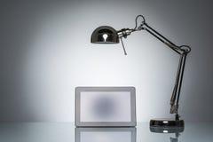 Iluminação acima da nota do touchpad da tabuleta com lâmpada de mesa fotos de stock royalty free