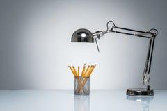 Iluminação acima dos artigos de papelaria alaranjados do suporte do lápis com lâmpada de mesa Imagens de Stock