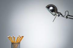 Iluminação acima dos artigos de papelaria alaranjados do suporte do lápis com lâmpada de mesa Fotos de Stock