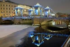 Iluminação da noite da ponte de Lomonosov através do rio de Fontanka Opinião do inverno fotos de stock royalty free