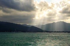 Iluminação do por do sol através de um céu nebuloso sobre o oceano fotos de stock