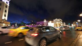 Iluminação dos feriados do Natal e do ano novo e tráfego dos carros na rua de Tverskaya do centro da cidade de Moscou perto do Kr filme