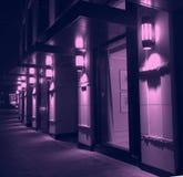 Iluminação violeta da noite da fachada moderna da construção da cidade imagens de stock royalty free