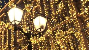 Iluminación brillante de la calle de la Navidad La ciudad se adorna para el día de fiesta de las Navidades Luces del Año Nuevo qu almacen de metraje de vídeo