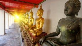 Iluminación de efecto de la llamarada sobre Buda de oro en pasillo Foto de archivo libre de regalías