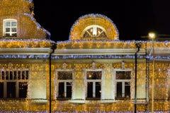 Iluminación de la Navidad en un edificio altos piso y tejado Todas las paredes adornadas con las guirnaldas Fotos de archivo libres de regalías