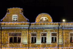 Iluminación de la Navidad en un edificio altos piso y tejado Todas las paredes adornadas con las guirnaldas Imagen de archivo