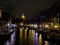 Iluminación de la noche de edificios cerca del agua en el canal en Amsterdam Foto de archivo