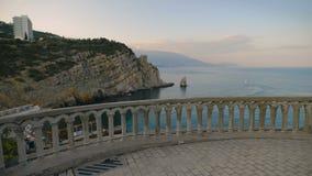 Iluminación de la puesta del sol, un balcón con las vistas del estado en las rocas y el mar almacen de metraje de vídeo