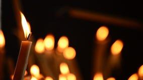 Iluminación de la vela con las velas defocused en fondo almacen de metraje de vídeo