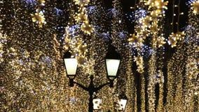 Iluminación de los días de fiesta de la Navidad y del Año Nuevo al aire libre en calle de la ciudad en la noche Guirnaldas brilla almacen de metraje de vídeo