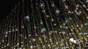 Iluminación de los días de fiesta de la Navidad y del Año Nuevo al aire libre en calle de la ciudad en la noche Guirnaldas brilla almacen de video