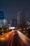 Iluminación del vehículo en el camino y el edificio urbanos contra escena de la noche Fotos de archivo libres de regalías