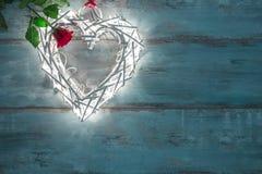 Iluminaciones de las tarjetas del día de San Valentín en la forma de un corazón en una rosa de madera del fondo y del rojo Fotografía de archivo