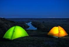Iluminado das barracas alaranjadas e verdes do interior no monte acima do riv fotos de stock