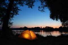 Iluminado do interior da barraca alaranjada na costa do lago entre silhuetas das árvores foto de stock royalty free