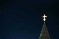 Iluminando a cruz ortodoxo em um céu azul Fotografia de Stock