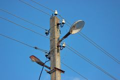 Iluminando o mastro com luzes e fios polo concreto da eletricidade com muitas conexões ao fio contra um céu ensolarado azul imagens de stock