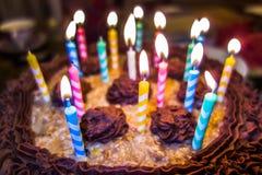 Iluminando velas coloridas no bolo de aniversário Imagens de Stock Royalty Free
